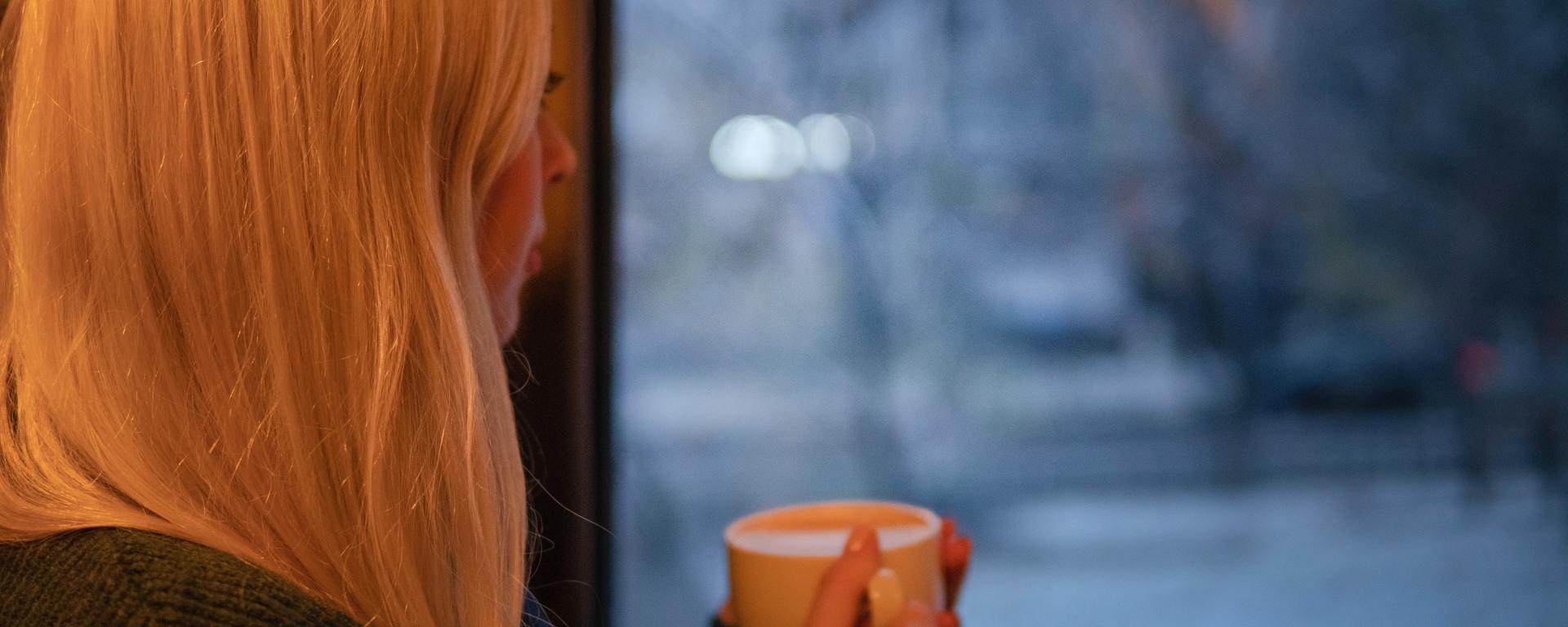 woman holding mug and looking out window