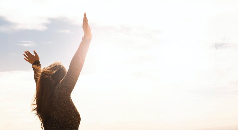 girl with arms raised facing the sun
