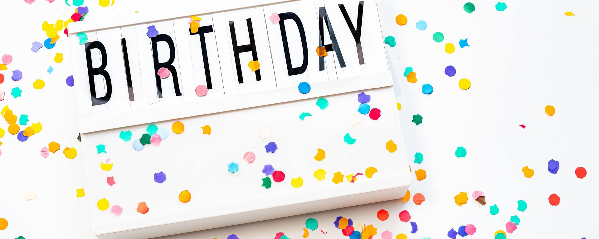 """white sign that reads """"birthday"""" in black letters surrounded by colorful confetti on a white background"""