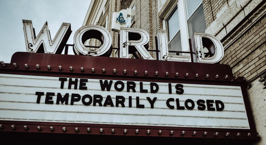 """world theater marquee sign that reads """"the world is temporarily closed"""""""