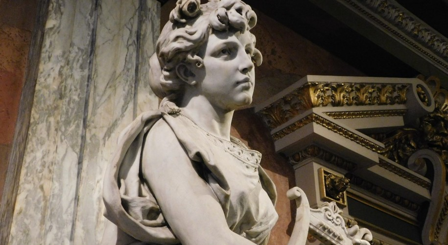marble muse holding a harp in front of a marble column and ornate archway