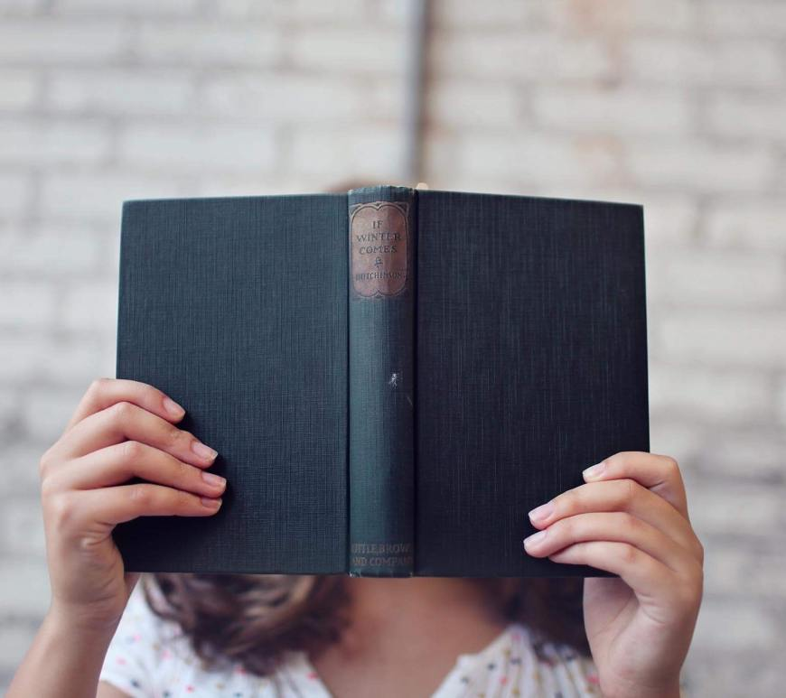 Woman holding open book in front of her face