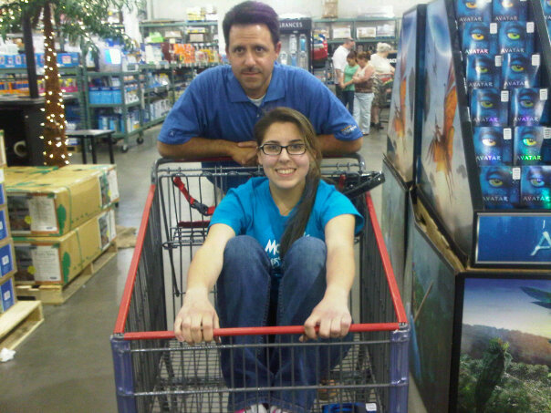 renata in a shopping cart smiling at the camera while her dad is pushing the shopping cart