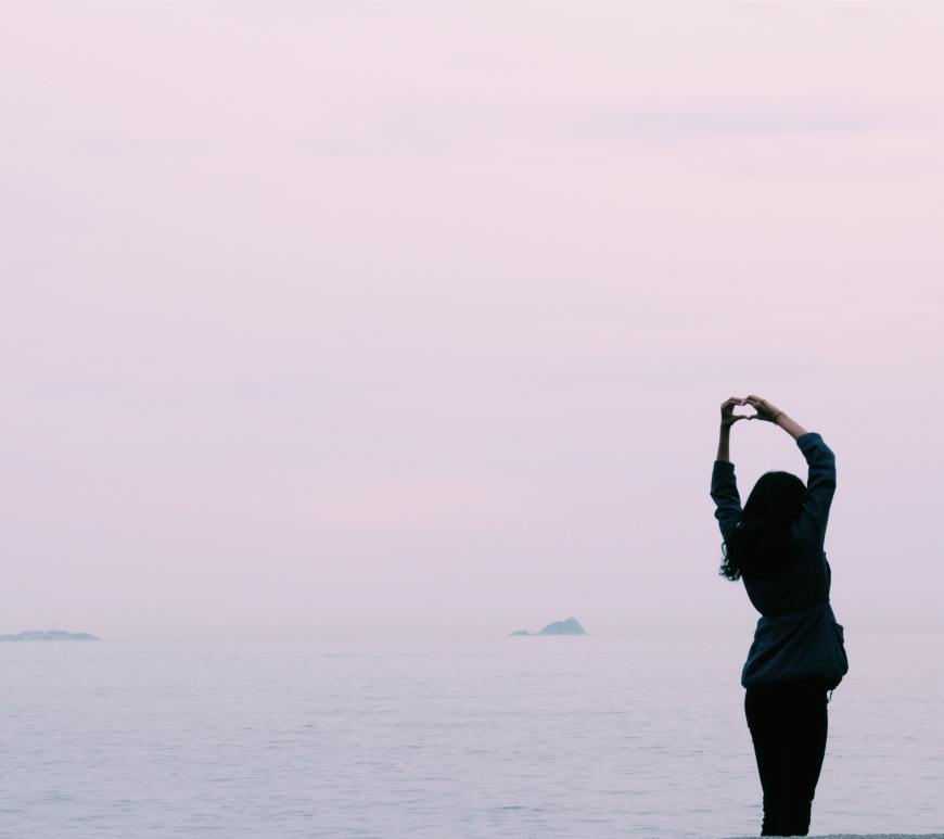 woman standing facing the water with her hands above her head in a heart sign