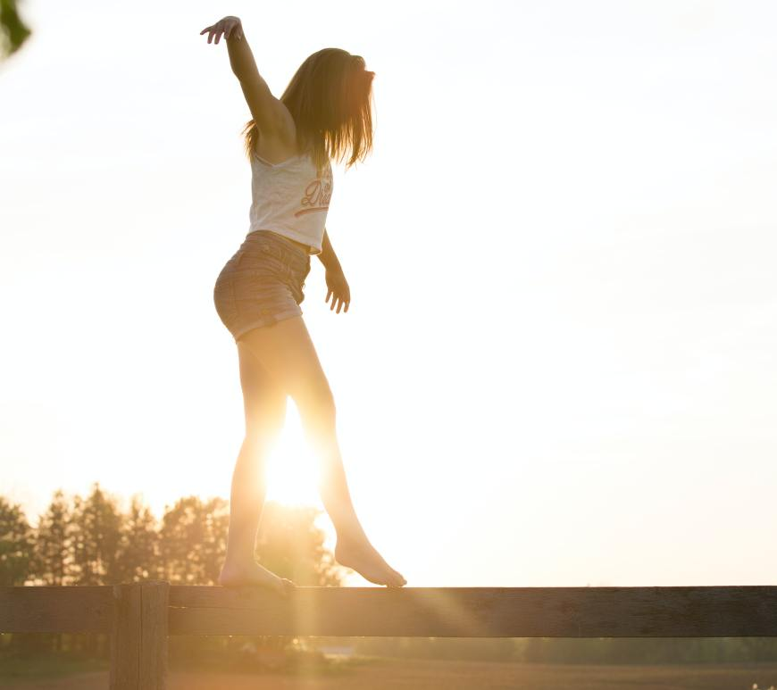 woman in a tank top and shorts walking across a wooden fence like a balance beam with the sun and trees in the background