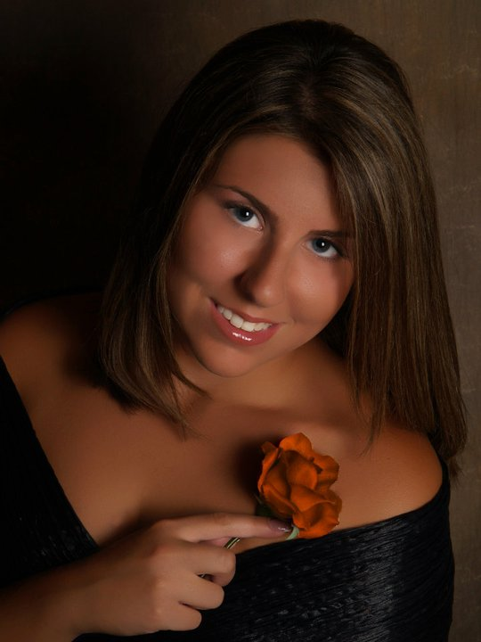 renata holding a rose with a black dress on