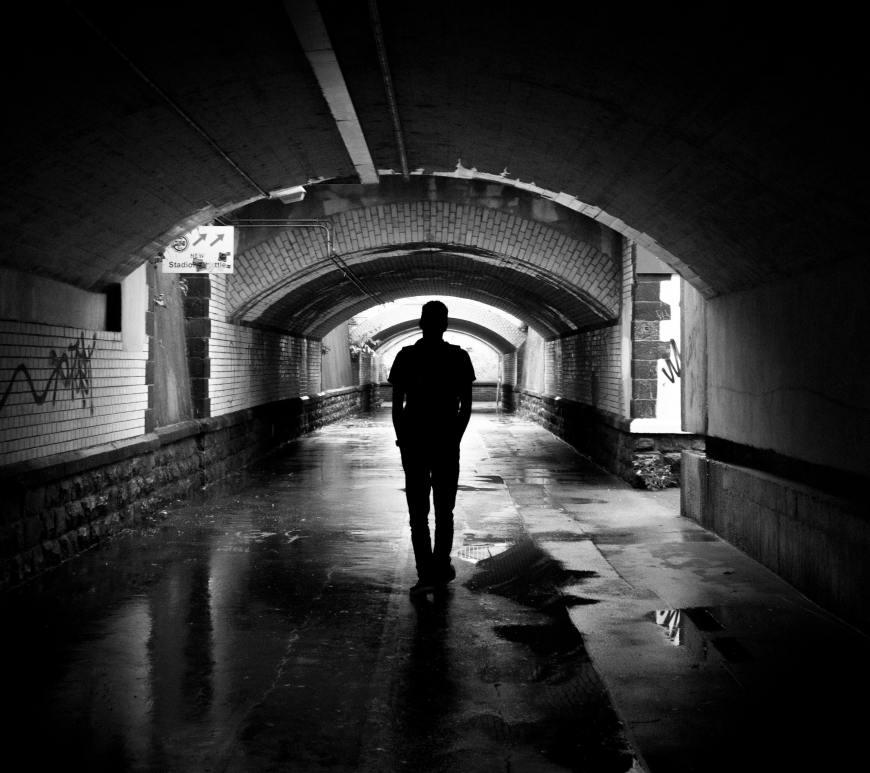 silhouette of man walking through tunnel