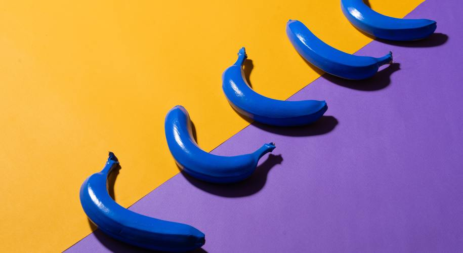 5 blue bananas on a yellow and blue background