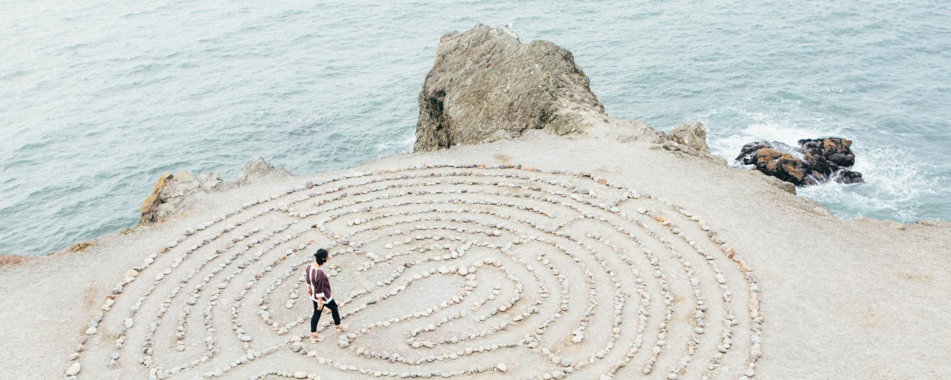 person walking through a circular stone maze in the sand by the ocean