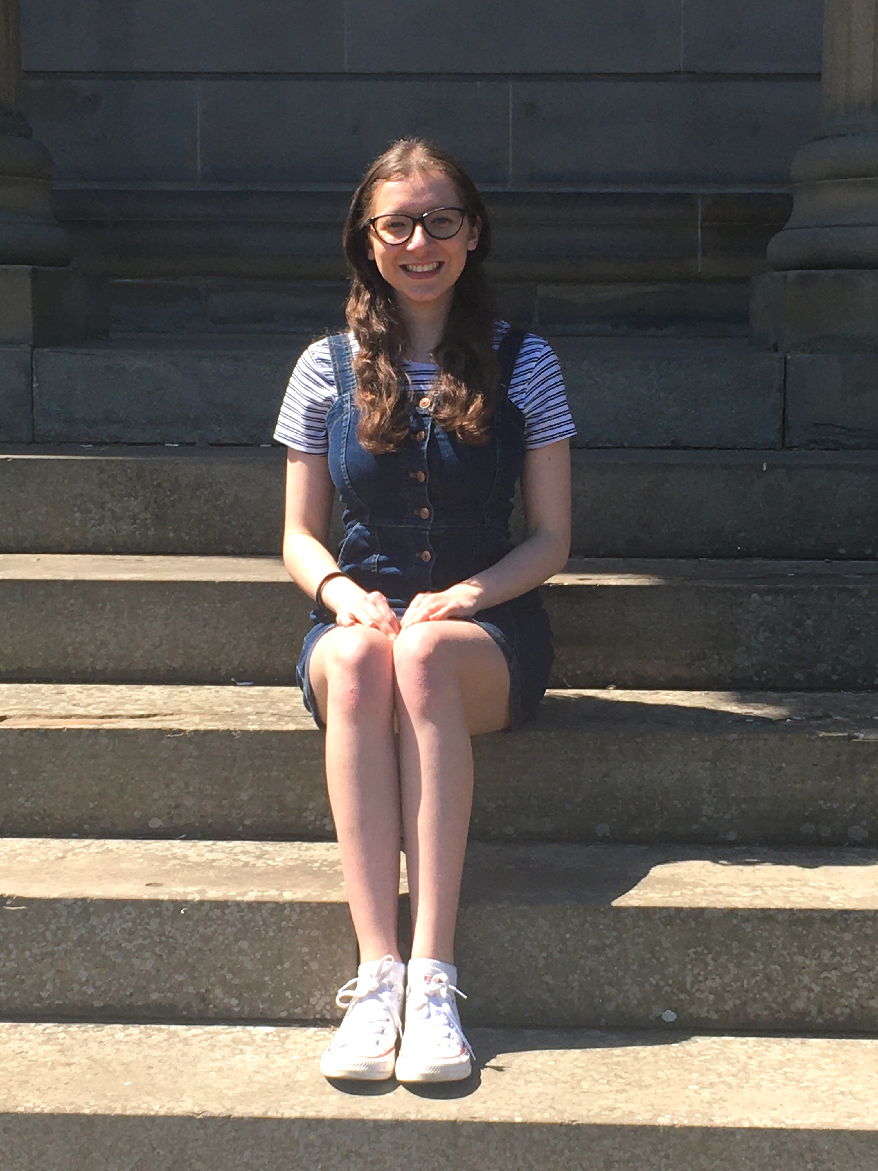 girl with long hair and glasses sitting on steps in a striped shirt, denim jumper, and white sneakers