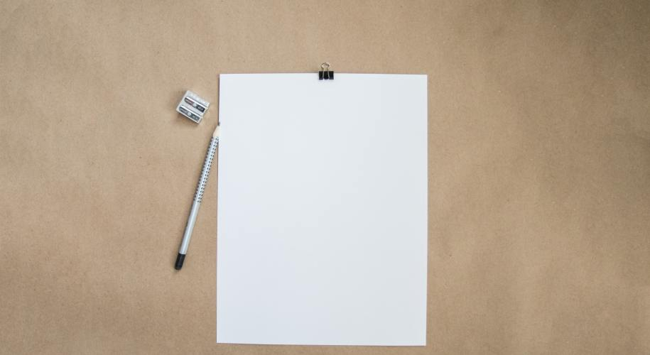 paper, pencil, and sharpener on a tan background