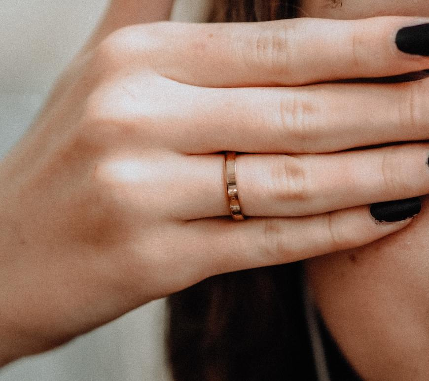 woman with dark hair holding her fingers over her eye and cheek with black nails and a gold ring on her ring finger
