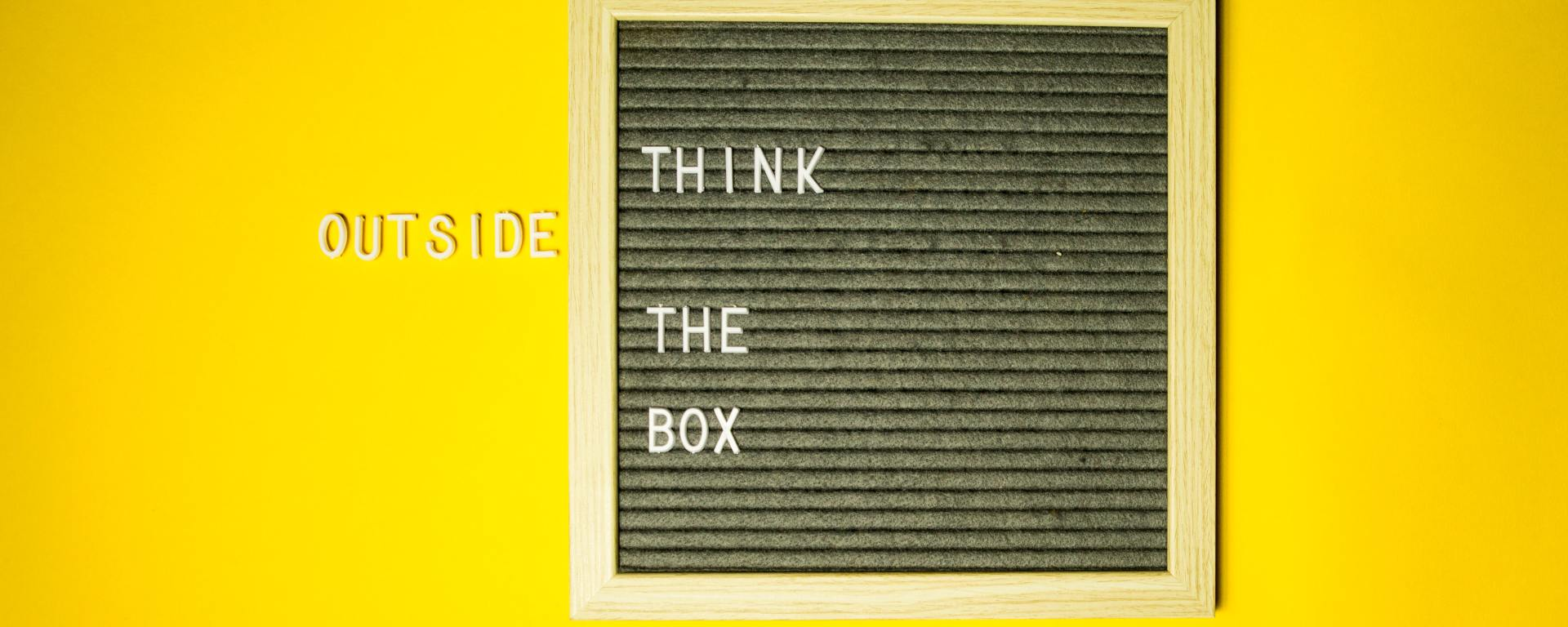 """board with the words """"think"""" """"the"""" and """"box"""" with the word """"outside"""" outside the box all on a yellow background"""