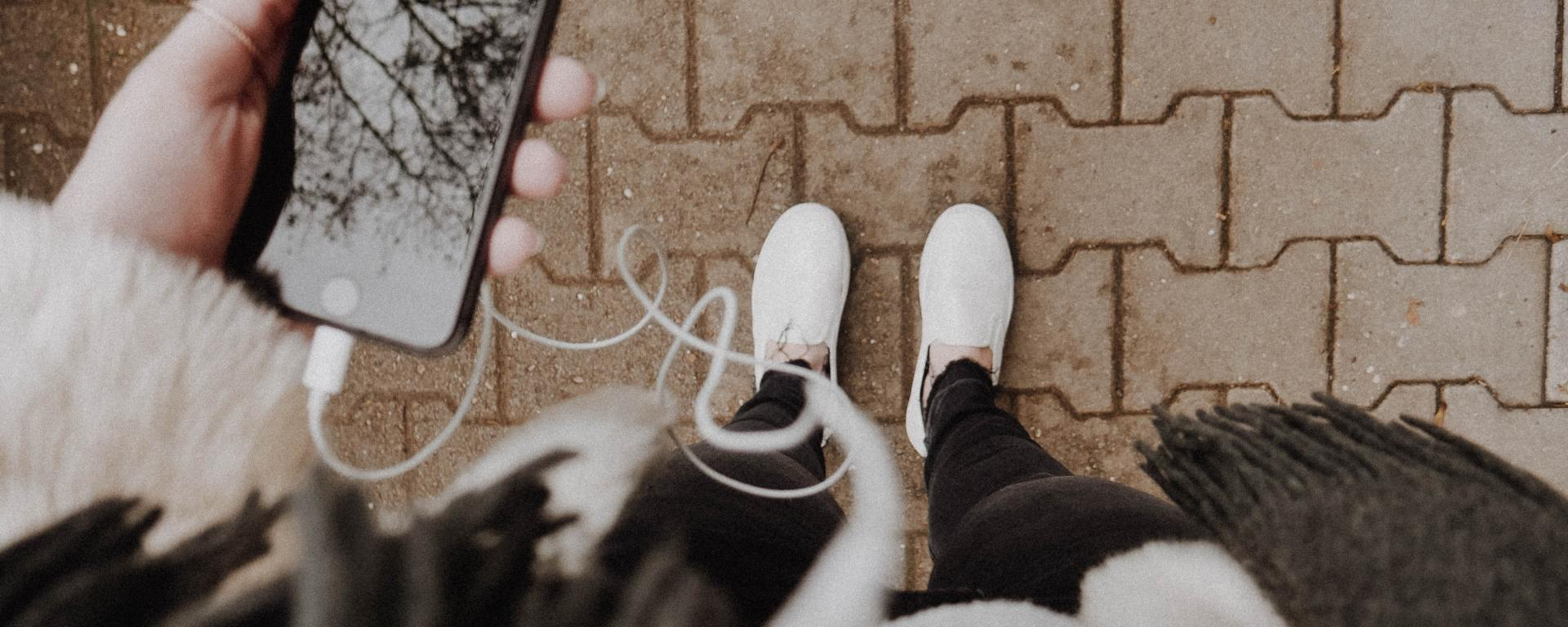 image facing down to someone's white shoes while they hold an iphone with headphones